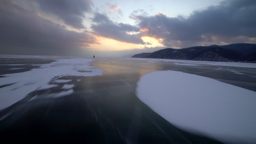 Unidentified man rides his bike, on frozen lake during winter. Magnificent landscape. The sunset covered with clouds on the lake Baikal. Fast movement.