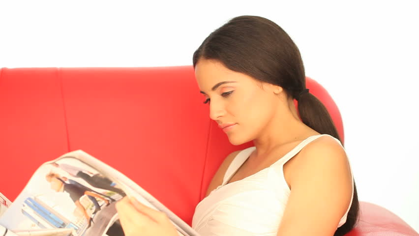 Woman reading a magazine on a sofa