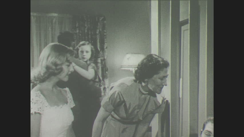 1940s: Woman introduces young woman to young man at party. Young man and woman dance in living room party. Young man and woman sit on couch, watch a film of man falling down stairs.