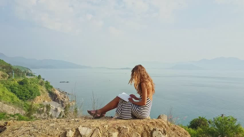 Flycam removes from girl sitting on hill top and reading book against boundless peaceful ocean and tropical nature