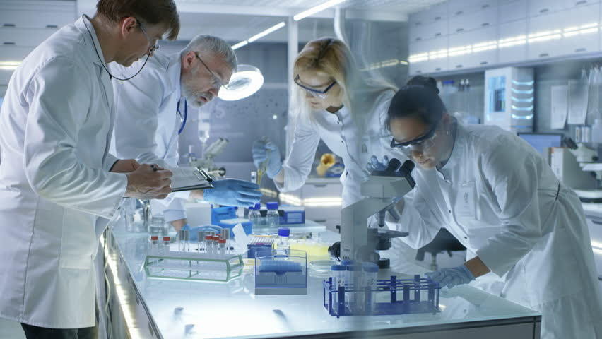 Team of Medical Research Scientists Work on a New Generation Disease Cure. They use Microscope, Test Tubes, Micropipette and Writing Down Analysis Results. Laboratory Looks Busy, Bright and Modern. 4K
