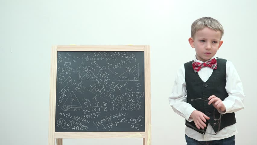 Amusing child setting his eyeglass and looking at chalk board, thinking at different solutions, heavy work, fancy boy dressed with uniform and bow, blackboard written with math formulas | Shutterstock HD Video #29111440