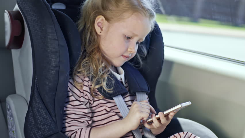 Cute little girl swiping on screen of smartphone while riding in car seat #29130340