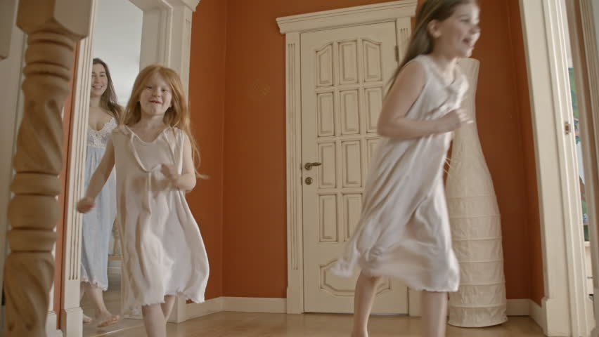 Low angle slow motion shot of happy little girls in nightdresses running from bedroom followed by their young smiling mother while elderly father carrying boy intro bathroom in morning