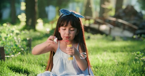Happy little Asian girl blowing soap bubbles in spring Park. Slow motion