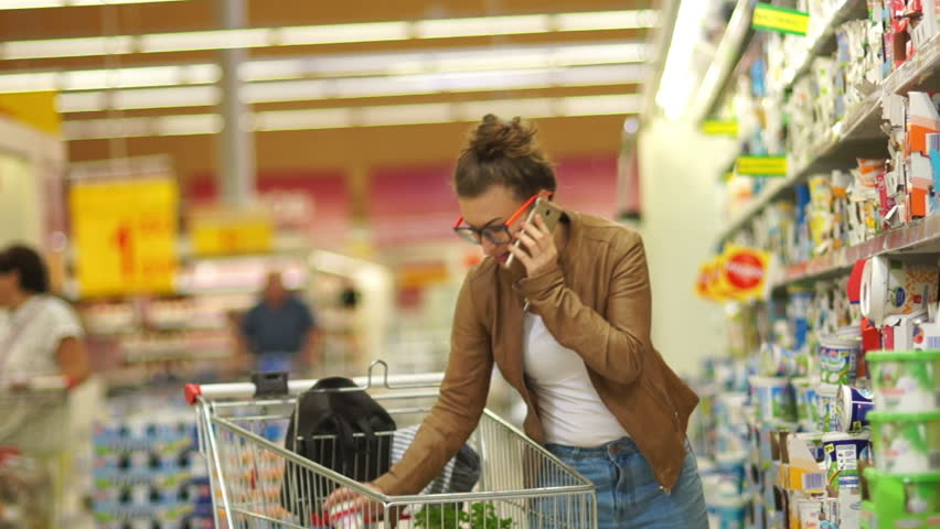 Beautiful woman buys kefir in a supermarket. Young Mommy, Housewife, Milk Diet, Milk Proteins, Difficult Choice, Healthy Eating. The girl is talking on the mobile | Shutterstock HD Video #29149726