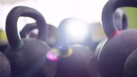 PAN with lens flare of row of cast-iron kettlebells standing in empty gym on sunny day