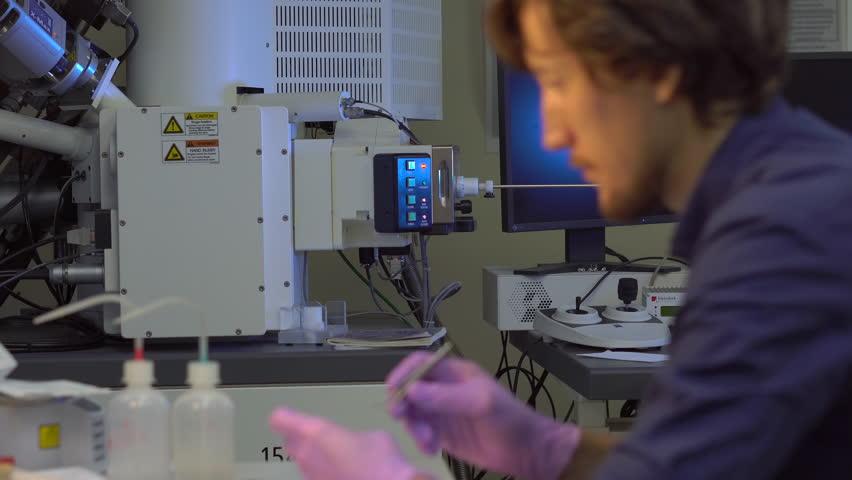 Scientist in a laboratory prepares samples for electron microscopy investigation