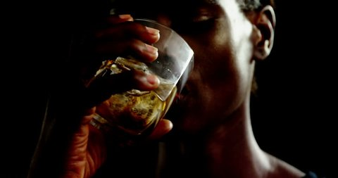 Portrait of androgynous african-american man drinking whiskey against black background