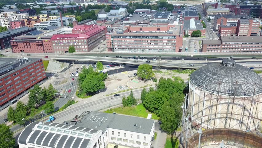 4K aerial view drone footage of Suvilahti old energy production industrial area with large old gasometers and city skyline, highways, roads and urban view in the capital of Finland, northern Europe