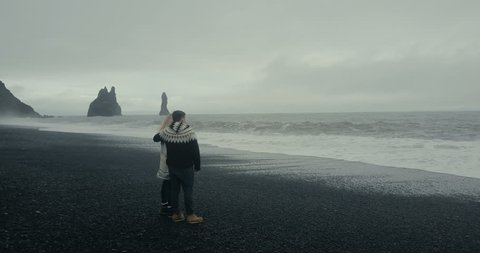 Aerial view of young couple standing on the black volcanic beach near the troll toes rock and looking on wave in Iceland