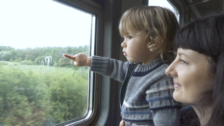 Train departs from station. Little curious boy and her mother looking out of window in train. Drops of rain on glass. It's raining outside, people reflecting in glass.