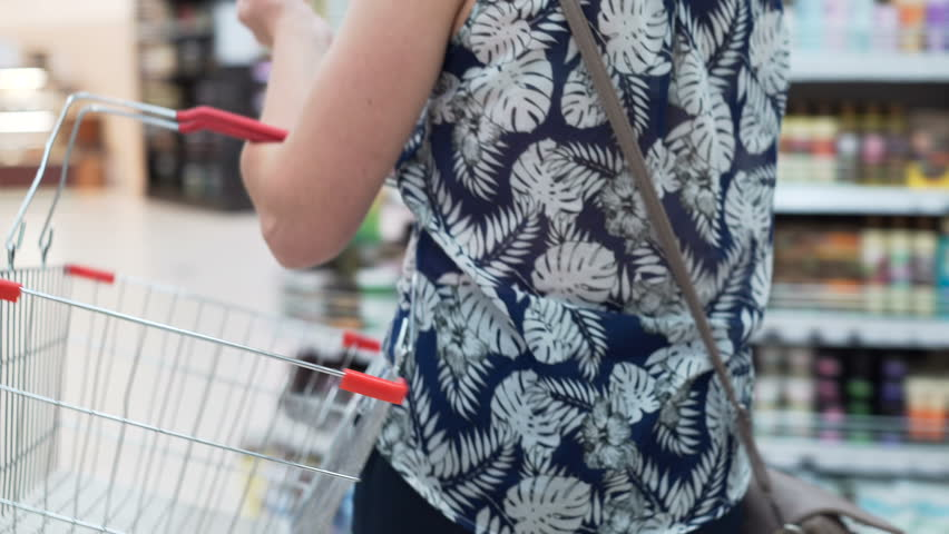 Closeup isolated shot of shop's iron handcart indoor. Woman's hand carry bag. Mistress slowly going between shelves and selecting the good in big modern marketplace