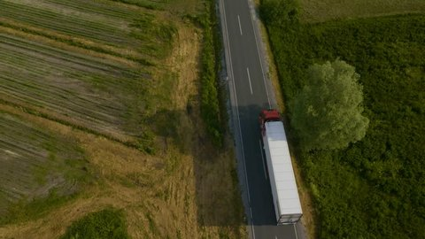 Aerial shot of a truck on the road driving away in beautiful countryside with green grass in the summer.