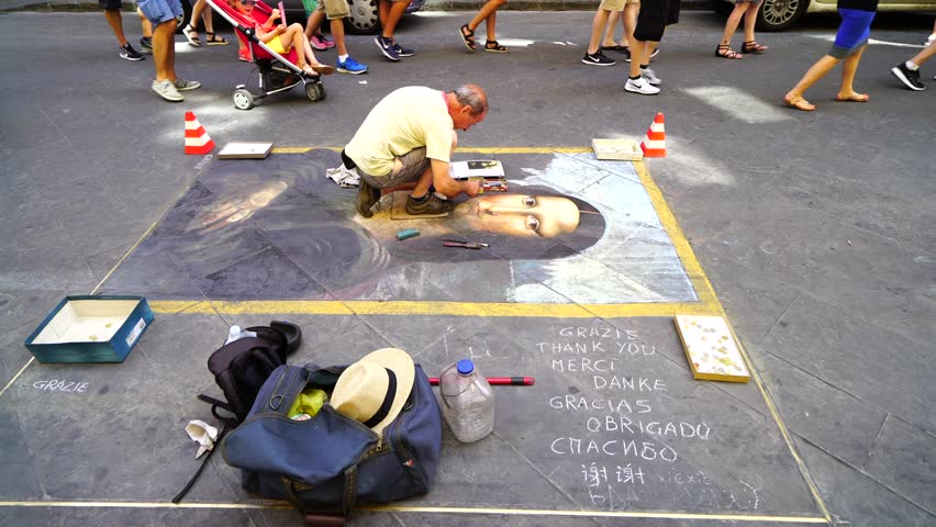 An artist paints Mona Lisa in the streets of Florence Italy, near the Uffizii museum working for tips. July of 2017 Tourists help support street vendors, artists and hustlers alike.