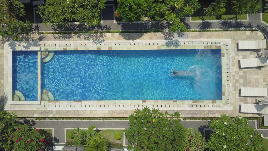 AERIAL SLOW MOTION TOP DOWN: Woman on summer vacation jumping head first into blue pool water for refreshment on hot sunny day. Girl in pink bikini diving and swimming in empty pool at luxury resort