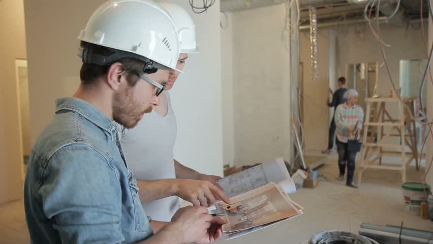 Among the repairs, two men in helmets discuss a project on securities. The construction team works for the reconstruction of the premises. People around color, clean and clean. A tall customer with a | Shutterstock HD Video #29303710