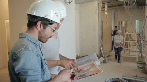 Among the repairs, two men in helmets discuss a project on securities. The construction team works for the reconstruction of the premises. People around color, clean and clean. A tall customer with a