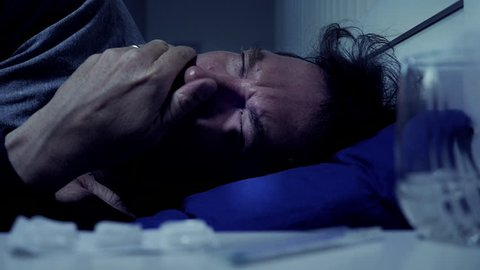 Man at night in bed coughing strong sick