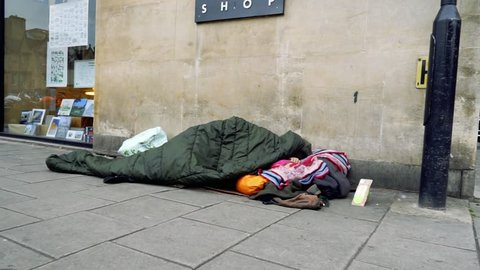 Poor socially excluded disadvantaged person sleeping on the pavement sidewalk in a street in Oxford England