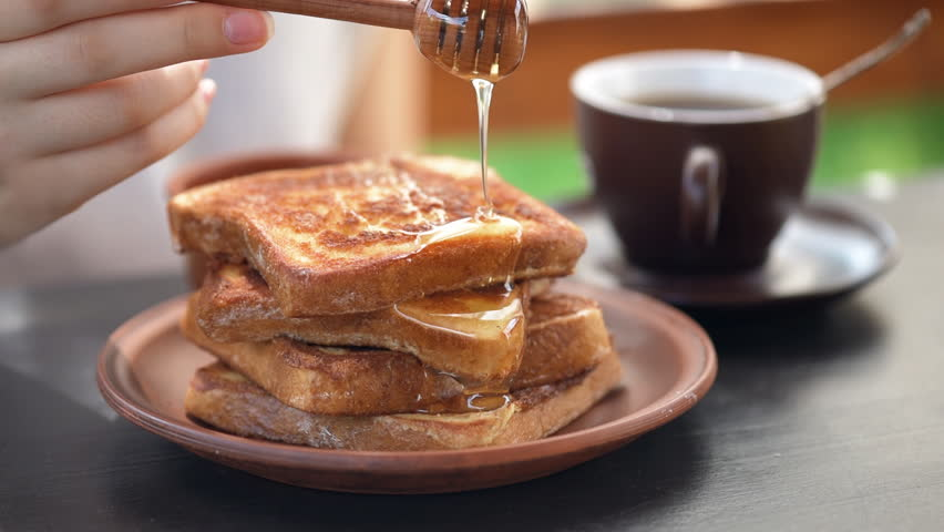 Cinemagraph -French toasts with honey. Healthy breakfast. Motion Photo.