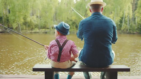 Grandfather and his grandson are casting lines during salmon fishing on the river