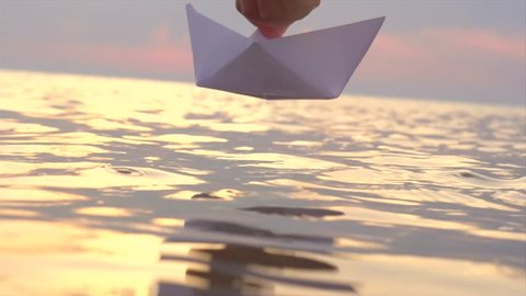 Kid putting a paper boat into water over beautiful sunset. Little boy's hand puts paper ship on sea surface. Slow motion 4K