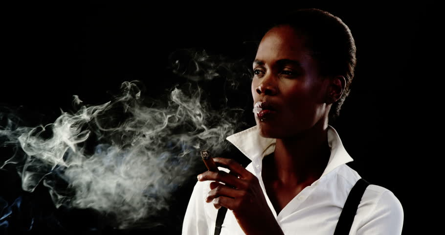 Confident androgynous man smoking cigar against black background