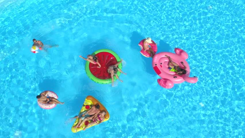 AERIAL: Cheerful friends having water fight on colorful floaties at pool party. Playful guys and girls splashing water and taking selfies on inflatable pizza, doughnut, flamingo and watermelon floats
