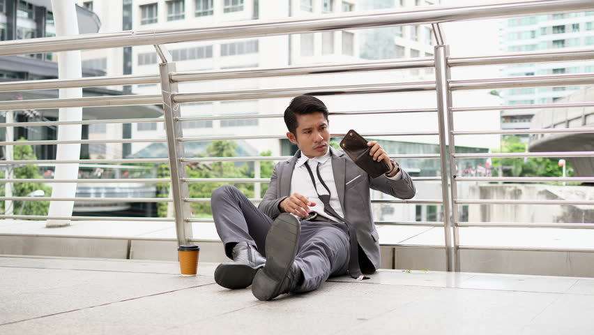 Poverty or bankruptcy concept - Asian Businessman having no money in pocket and unemployed. Urban background
