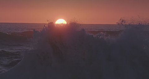 Waves crashing rocky shoreline as sun is setting on piha beach, auckland, New Zealand