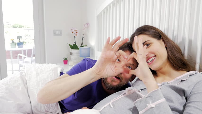 Pregnant couple in bed making love sign looking camera