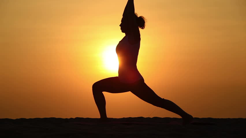 Slim woman doing yoga over orange sun
