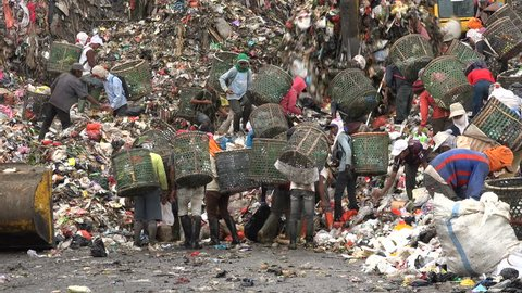 JAKARTA, INDONESIA - APRIL 2017: People scavenge for items to recycle at garbage dump site in Jakarta, tough working conditions in Indonesia