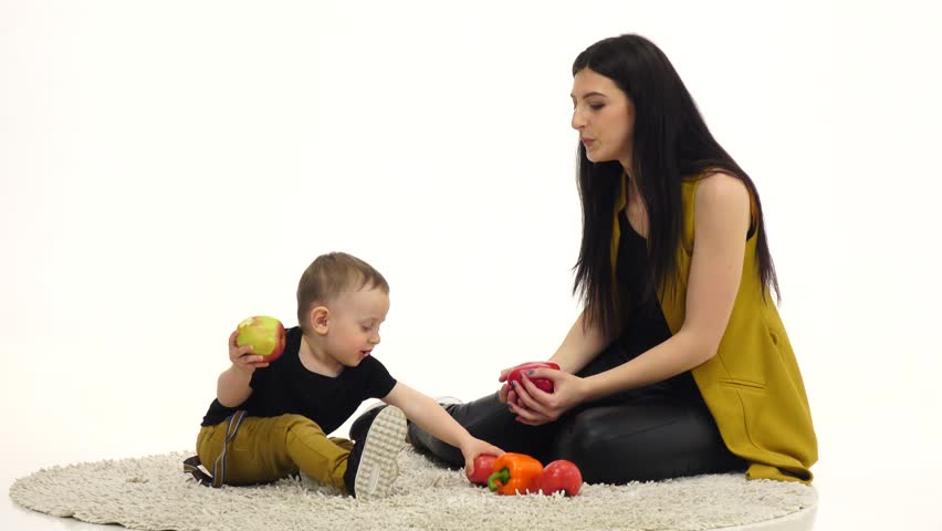 Mom and child are sitting on the floor, around a lot of vegetables and fruits. White background | Shutterstock HD Video #29480950