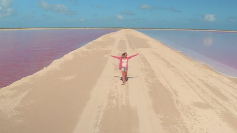 AERIAL, CLOSE UP: Attractive young female walking along the sandy levee surrounding amazing pink lakes of Las Colorado on hot sunny day in Mexico. Tourist girl on vacations strolling along salinas