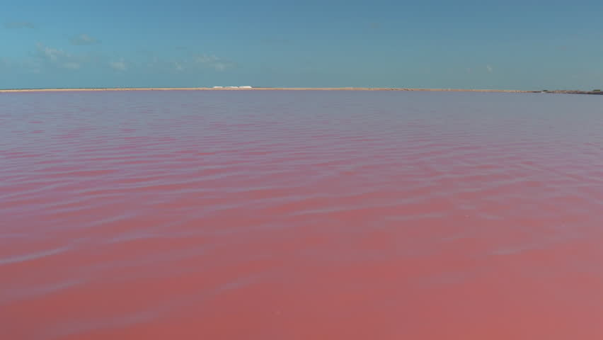 AERIAL, CLOSE UP: Flying close above the water surface of amazing pink lakes of Las Coloradas, Mexico. Beautiful red, orange and violet saltworks. Stunning colorful salt evaporation ponds, Yucatan
