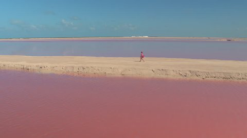 AERIAL, CLOSE UP: Tourist girl in pink cardigan walking down the sandy levee watching gorgeous pink lagoons and salt mountains. Woman enjoying summer vacations viewing amazing pink sea water salt pans