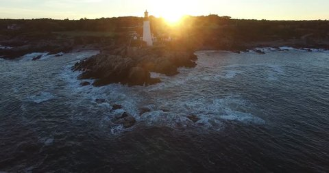 Lighthouse on Rocky Ocean Point during Sunset with Active Light - Aerial Footage of Portland Head Lighthouse, Maine, USA
