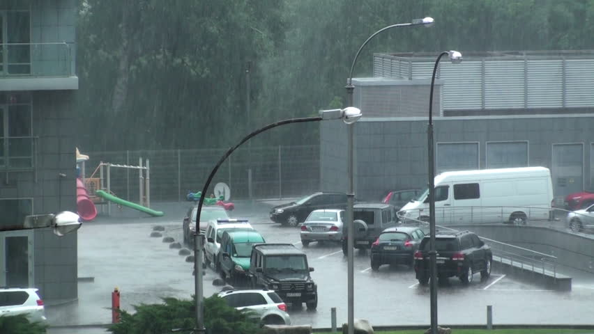 Heavy rain in the city. A very heavy downpour floods the cars in the parking lot next to the house. HD 1920x1080 Video Clip