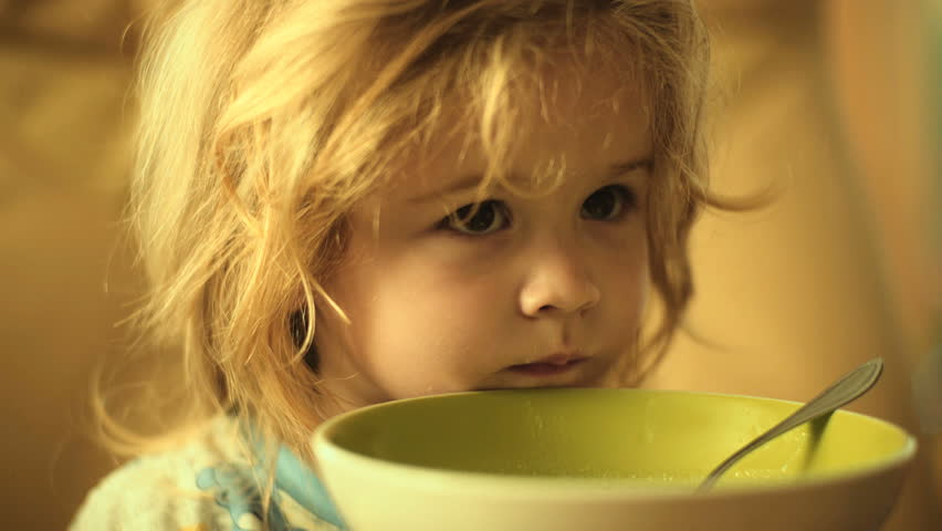 Breakfast child eats. Healthy diet for toddler. Cute boy with beautiful hair at home at table with spoon porridge or rice. Child eating oatmeal with milk. Concept healthy breakfast for children