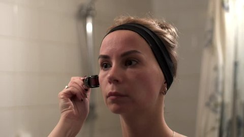 Young woman using a derma roller for micro needling therapy face. Mesoroller for micro facial massage. Roller, microneedle, mesotherapy. Facial treatment at home