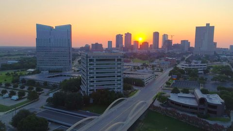 Aerial wide shot 2 fly to Fort Worth skyline at sunrise over Landmark 7th St. Bridge and Trinity River Park