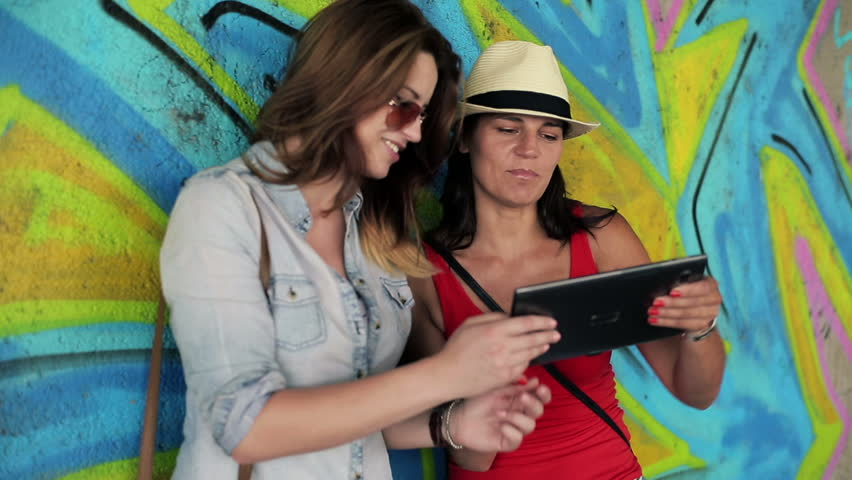 Female friends with tablet computer by graffiti wall, steadicam shot  | Shutterstock HD Video #2957530