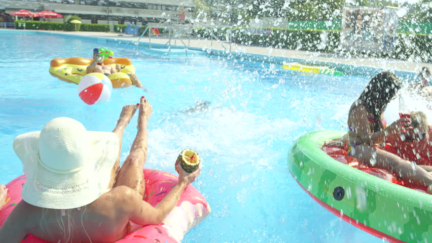 SLOW MOTION CLOSE UP Happy smiling students drinking alcohol cocktails on colorful floaties at pool party on spring break. Cheerful young people having fun on inflatable pizza, watermelon and doughnut