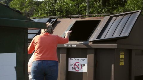 Middle Aged Woman throwing Recyclables into large receptacle