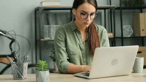 Young attractive businesswoman suffering from back pain while working with laptop computer in the modern office. Close up