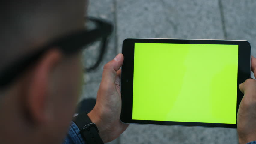 Close up shot of attractive man using tablet with green screen while sitting in the city. Chroma key. Horizontal position.