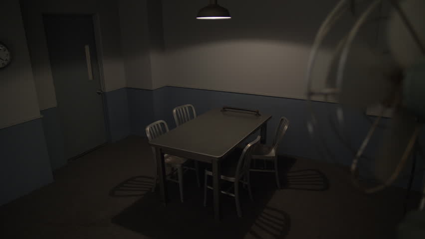 INTERROGATION ROOM.  No people.  High angle lock off with a slow turning fan in the foreground.