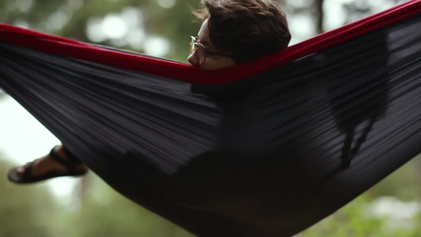 carefree camper relaxes in hammock swings gently back and forth slow motion   hd portrait of happy camper relaxing in hammock they adjust their      rh   shutterstock